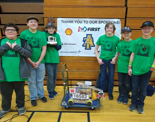 Picture of robotics club members with the robot they competed
