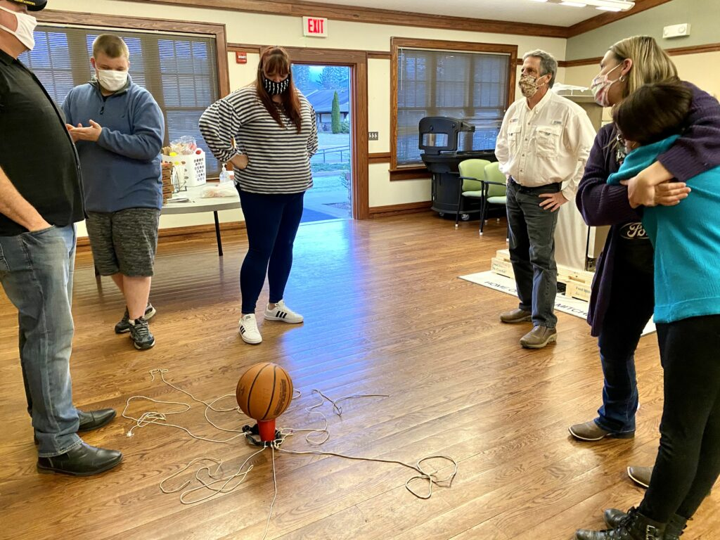 Participants standing around a basketball balanced on a cup.