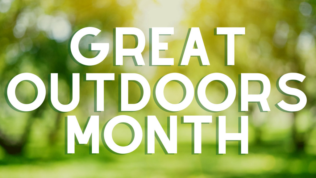 Great Outdoors Month in text on blurred tree background