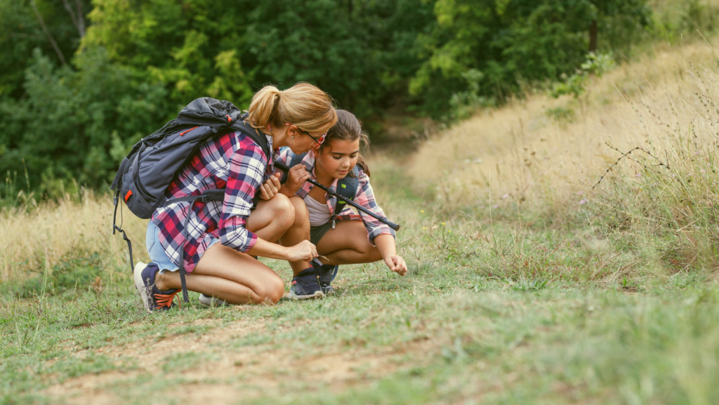 mother daughter hiking observing something on the ground